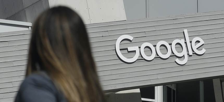 In this Sept. 24, 2019, file photo, a woman walks below a Google sign on the campus in Mountain View, Calif.