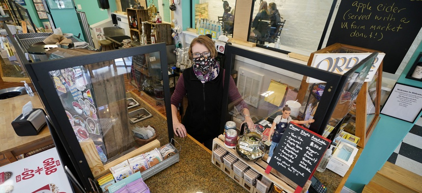 Victoria Leigh Kidd, owner of Hideaway Café, greets customers from behind protective shields in her shop in the Old Town area of Winchester, Va., Wednesday, Oct. 7, 2020.