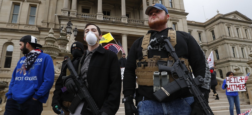 In this April 15, 2020 file photo, protesters carry guns outside the Capitol Building in Lansing, Mich.