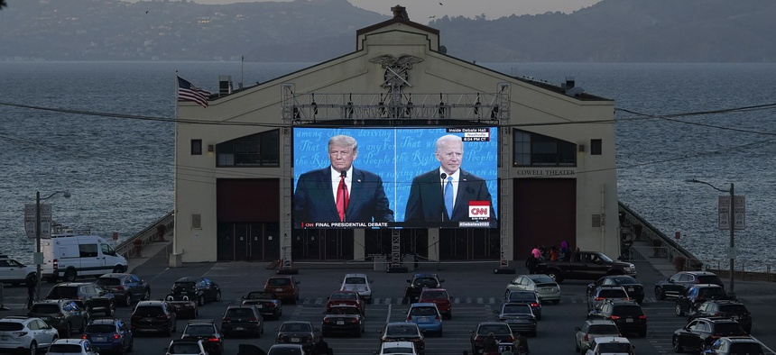 People watch from their vehicles as President Donald Trump, left, and Democratic presidential candidate former Vice President Joe Biden speak during a Presidential Debate Watch Party at Fort Mason Center in San Francisco, on Oct. 22, 2020.