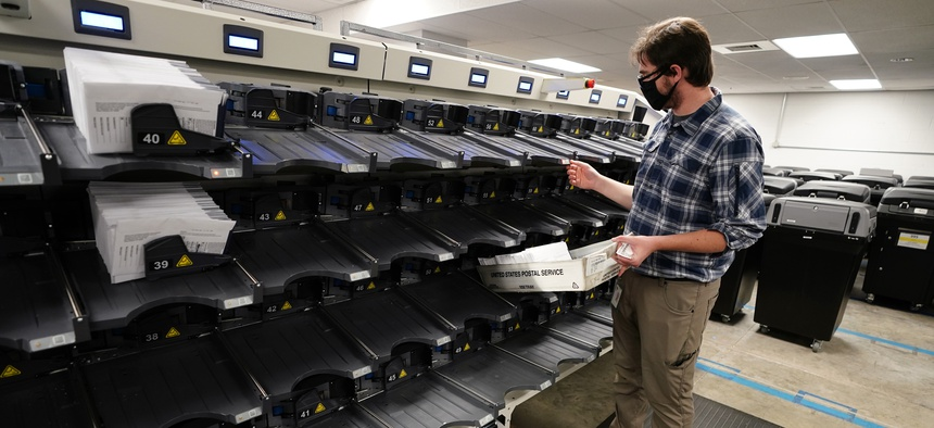 Michael Imms, with Chester County Voter Services, gathers mail-in ballots being sorted for the 2020 General Election in the United States, Friday, Oct. 23, 2020, in West Chester, Pa.