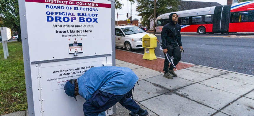 A District of Columbia Board of Election employee locks and seals an official ballot drop box after collecting ballots in northwest Washington, Thursday, Oct. 29, 2020. (AP Photo/Manuel Balce Ceneta)