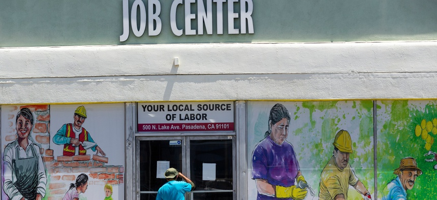 In this May 7, 2020 file photo, a person looks inside the closed doors of the Pasadena Community Job Center in Pasadena, Calif., during the coronavirus outbreak.