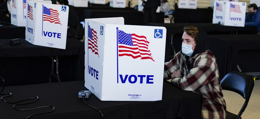 A voter casts his ballot during voting at a poling place inside Bankers Life Fieldhouse on Election Day in Indianapolis, Tuesday, Nov. 3, 2020.