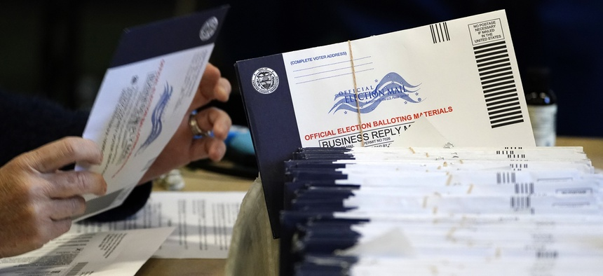 Chester County, Pa. election workers process mail-in and absentee ballots at West Chester University, Wednesday, Nov. 4, 2020, in West Chester.