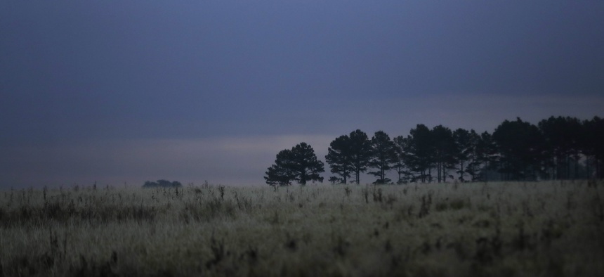 The sun peeks through clouds behind a group of trees as a thunderstorm fills the sky in Dawson, Georgia, in April. The county and other parts of rural southwest Georgia had high rates of deaths from Covid earlier this year.