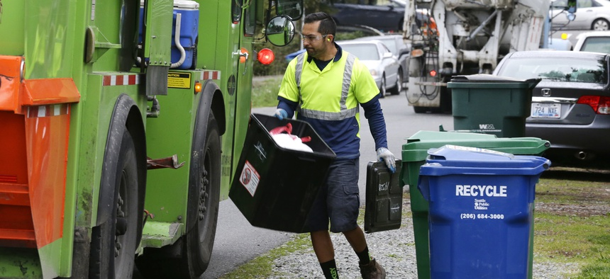 David Morales, a garbage driver with Recology, picks up a garbage container for Seattle Public Utilities, Friday, April 15, 2016, in Seattle.