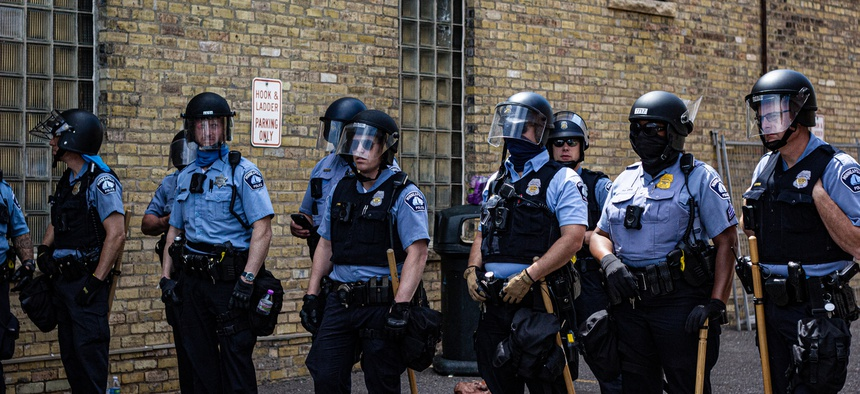 Minneapolis police stand near the Third Precinct in May. The department is under investigation by the state Human Rights Department.