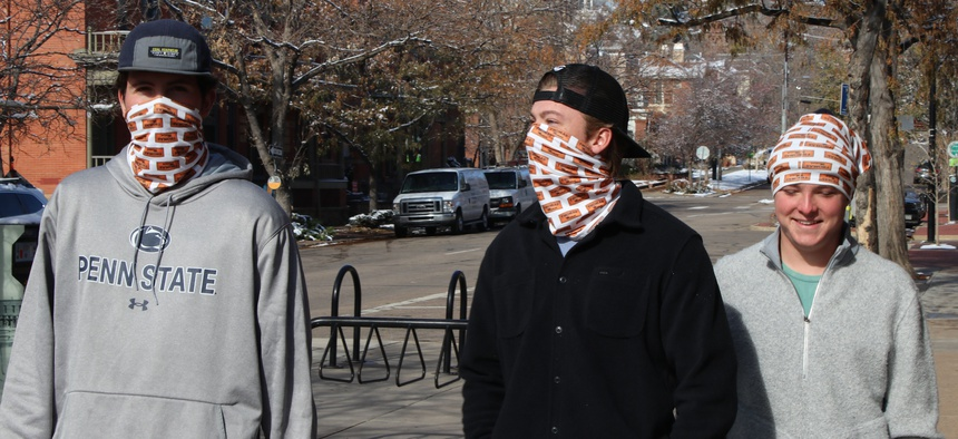 College students Colin Berg (left), Connor Dreher and Brady Bowman stroll through downtown Boulder, Colorado, in mid-November wearing matching neck gaiters.