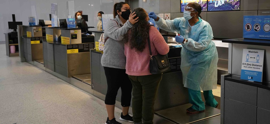 A nurse collects a nasal swab sample from a traveler at a COVID-19 testing site at the Los Angeles International Airport in Los Angeles, Monday, Nov. 23, 2020.