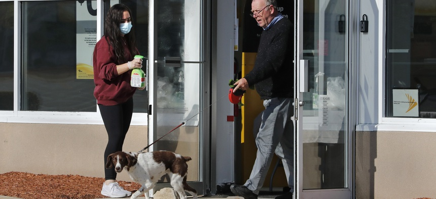 A masked worker at a mobile phone store sanitizes a door as an unmasked customer walks a dog out of the location in Nashua, N.H.