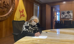 New Mexico Gov. Michelle Lujan Grisham signs a $330 million coronavirus relief package on Nov. 25, 2020.