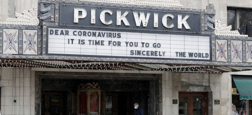 A man wears a mask as he walks in front of the Pickwick Theatre in Park Ridge, Ill., Tuesday, May 5, 2020. The cinema has been closed during the coronavirus pandemic.