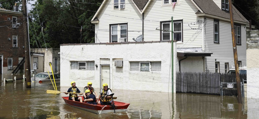 First responders make their way through floodwaters in Darby, Pa., Monday, Aug. 13, 2018.