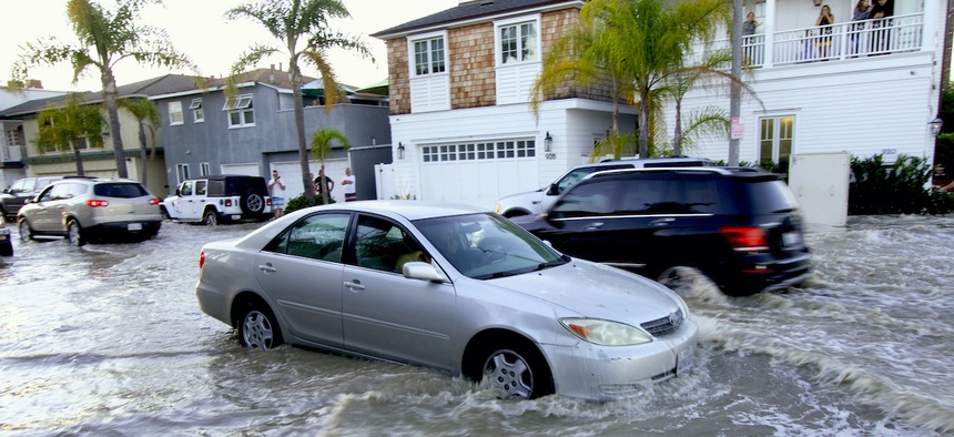 """Vehicles drive through flooded streets in Newport Beach, Calif., Friday, July 3, 2020. California is one of the states most vulnerable to climate change and is ranked """"more prepared"""" for its effects than other states in a new report."""