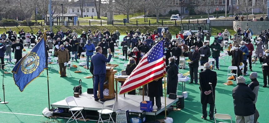 New Hampshire Gov. Chris Sununu, at podium, swears in lawmakers during an outdoor session, Wednesday, Dec. 2, 2020, at the University of New Hampshire in Durham, N.H.