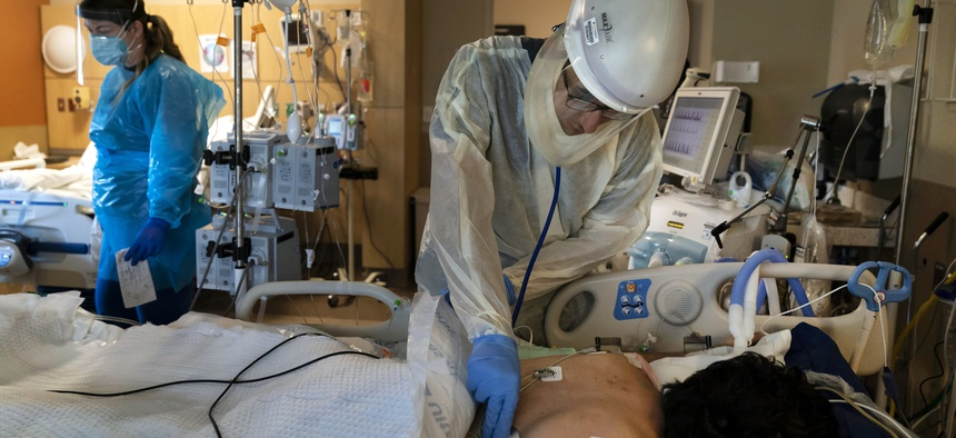 In this Nov. 19, 2020, file photo, Dr. Rafik Abdou checks on a COVID-19 patient at Providence Holy Cross Medical Center in the Mission Hills section of Los Angeles.