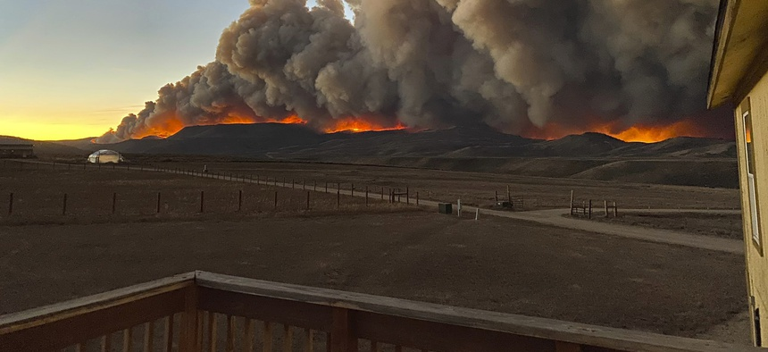A resident took this photo from the deck of her home north of Granby, Colo., just before sunset on Wednesday, Oct. 21, 2020 as a wildfire burned in the distance.