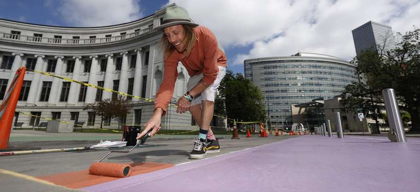 Artist Pat Milbery works to paint Denver's largest street mural on Bannock Street between Colfax Avenue and 14th Avenue in front of the City/County Building, Thursday, May 28, 2020.