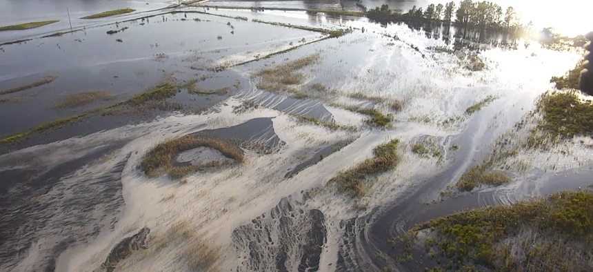 In this image made from 2018 drone video provided by the North Carolina DEQ, light gray material flows out of a flooded coal ash dump toward the Cape Fear River at Duke Energy's L.V. Sutton Power Station near Wilmington, N.C.