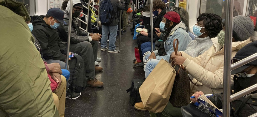 People ride on a subway train in New York City in December 2020.