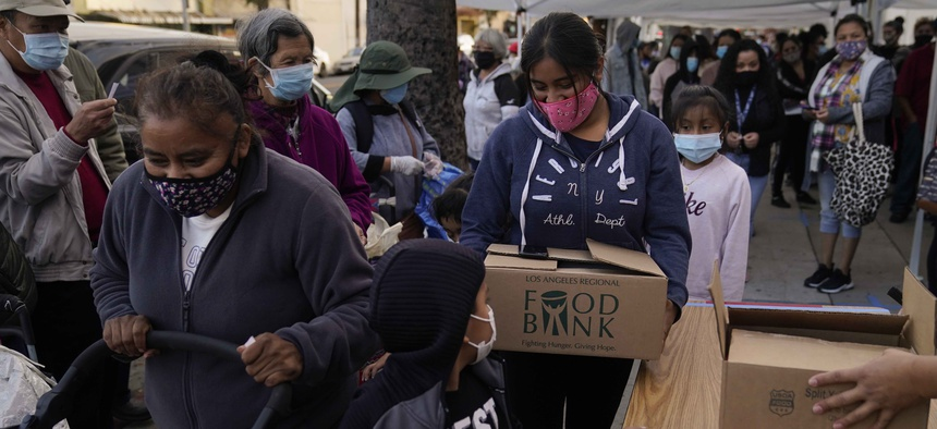 People pick up boxes of groceries at a food bank held at Los Angeles Boys & Girls Club in the Lincoln Heights neighborhood of Los Angeles, Thursday, Dec. 17, 2020.