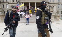 In this April 15, 2020, file photo protesters carry rifles near the steps of the Michigan State Capitol building in Lansing, Mich.