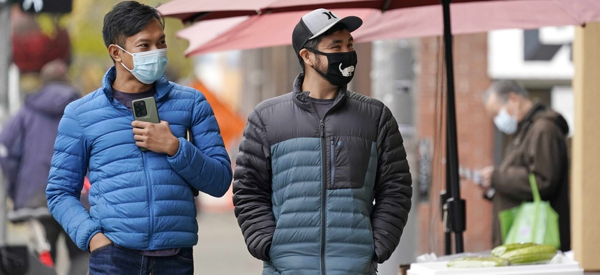 Pedestrians wearing masks walk past a small grocery store in the Chinatown-International District Thursday, Nov. 12, 2020, in Seattle.