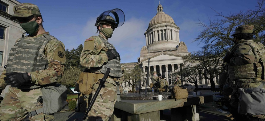 Members of the Washington National Guard stand at a sundial near the Legislative Building, Sunday, Jan. 10, 2021, at the Capitol in Olympia, Wash.