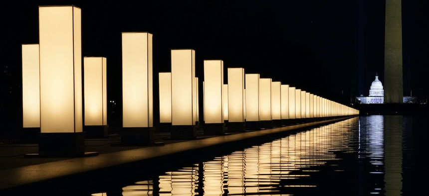 Lights surround the Lincoln Memorial Reflecting Pool, placed as a memorial to COVID-19 victims Tuesday, Jan. 19, 2021, in Washington, after President-elect Joe Biden spoke, with the Washington Monument and the U.S. Capitol in the background.