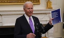 President Joe Biden holds a booklet as he speaks about the coronavirus in the State Dinning Room of the White House, Thursday, Jan. 21, 2021, in Washington.