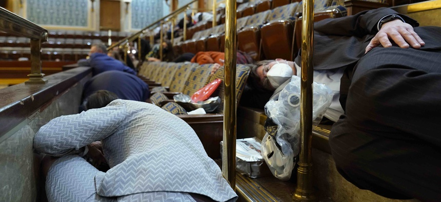 In this Wednesday, Jan. 6, 2021 file photo, people shelter in the House gallery as rioters try to break into the House Chamber at the U.S. Capitol in Washington.