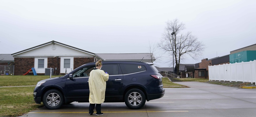 A registered nurse administers a Covid-19 test to a drive-up patient outside Scotland County Hospital Tuesday, Nov. 24, 2020, in Memphis, Mo.