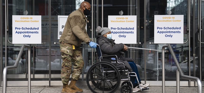 Patients are offered wheel-chairs by the National Guard at a COVID-19 vaccination site inside the Jacob K. Javits Convention Center, Wednesday, Feb. 3, 2021, in the Manhattan borough of New York.