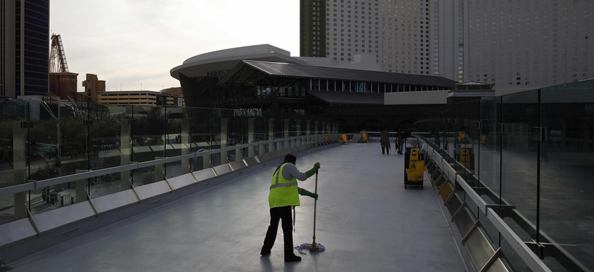 In this March 31, 2020, file photo, a worker cleans along the Las Vegas Strip devoid of the usual crowds when casinos and other business were shuttered due to the coronavirus outbreak in Las Vegas.