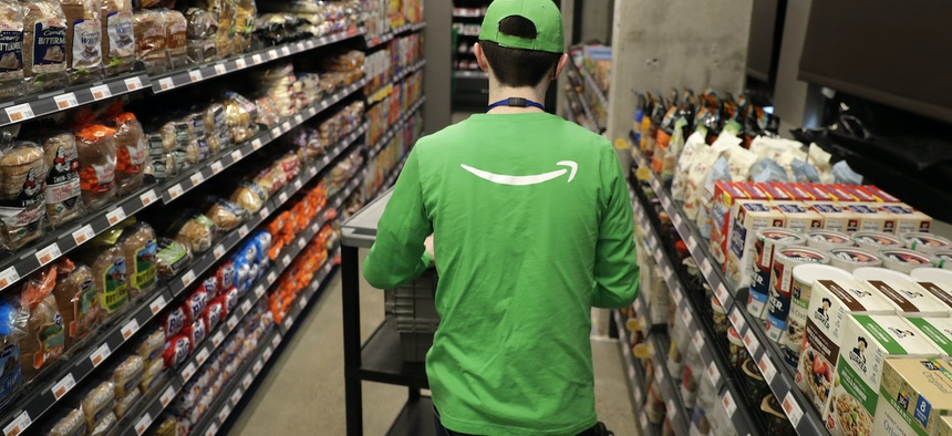 In this Feb. 21, 2020 photo, a worker pushes a cart inside an Amazon Go Grocery store set to open soon in Seattle's Capitol Hill neighborhood.