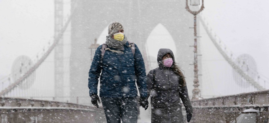 A couple walks on the Brooklyn Bridge, Monday, Feb. 1, 2021 in New York. A winter snowstorm walloped the Eastern U.S. on Monday.