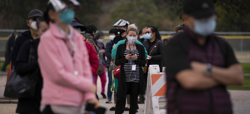People wait in line to get their COVID-19 vaccine at a vaccination site set up in a park in the Lincoln Heights neighborhood of Los Angeles, Tuesday, Feb. 9, 2021.