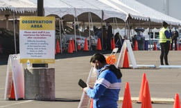 """Health workers at an """"Observation Area"""" wait for motorists being inoculated with a COVID-19 vaccine at the mass vaccination site at the parking lot of L.A. County Office of Education headquarters in Downey, Calif., Wednesday, Feb. 3, 2021."""