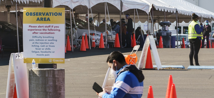 "Health workers at an ""Observation Area"" wait for motorists being inoculated with a COVID-19 vaccine at the mass vaccination site at the parking lot of L.A. County Office of Education headquarters in Downey, Calif., Wednesday, Feb. 3, 2021."