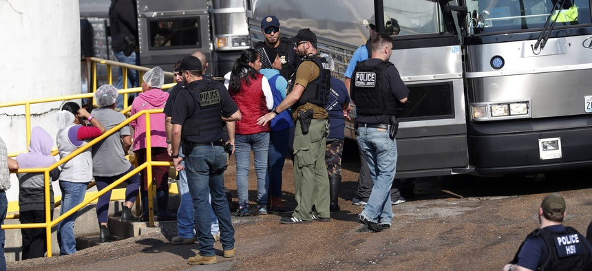 In this Wednesday, Aug. 7, 2019, file photo, handcuffed workers are escorted into a bus for transportation to a processing center following a raid by U.S. immigration officials at a Koch Foods Inc., plant in Morton, Miss.