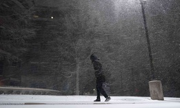 A woman walks through falling snow in San Antonio, Sunday, Feb. 14, 2021. Snow and ice blanketed large swaths of the U.S. on Sunday.