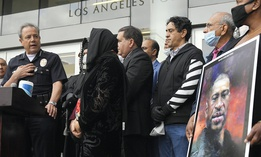 In this June 5, 2020, file photo, Los Angeles Police Chief Michel Moore, left, speaks as someone holds up a portrait of George Floyd during a vigil with professional associations and the interfaith community at Los Angeles Police Department headquarters.