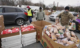 Sgt. Kevin Fowler organizes food at a food bank distribution by the Greater Cleveland Food Bank, Thursday, Jan. 7, 2021, in Cleveland.