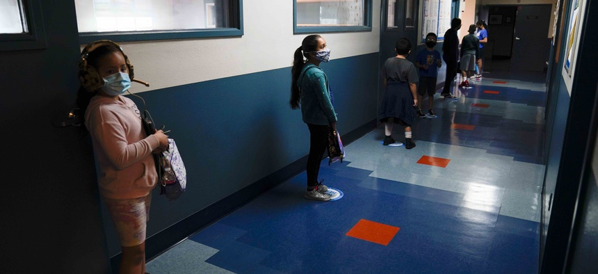 In this Aug. 26, 2020, file photo, Los Angeles Unified School District students stand in a hallway socially distance during a lunch break at Boys & Girls Club of Hollywood in Los Angeles.