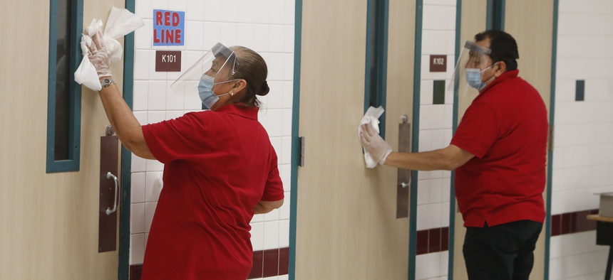 Wearing masks and face guards as protection against the spread of COVID-19, Garland Independent School District custodians wipe down surfaces at Stephens Elementary School in Rowlett, Texas, Wednesday, July 22, 2020.
