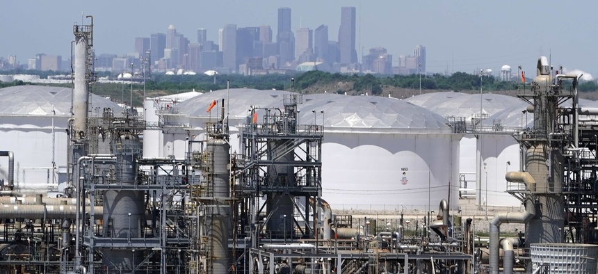 In this Thursday, April 30, 2020, photo storage tanks at a refinery along the Houston Ship Channel are seen with downtown Houston in the background.