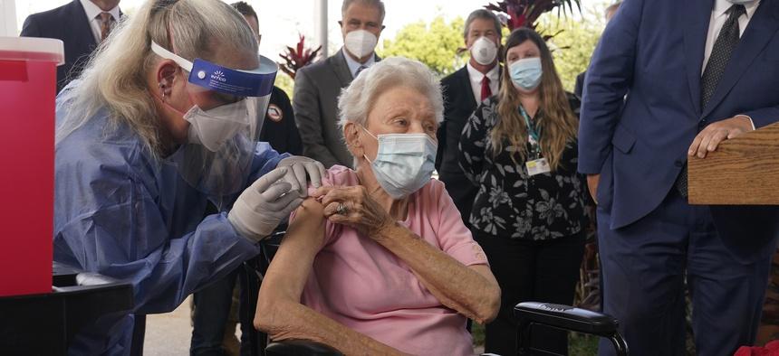 Nurse Christine Philips, left, administers the Pfizer vaccine to Vera Leip, 88, a resident of John Knox Village, Wednesday, Dec. 16, 2020, in Pompano Beach, Fla.