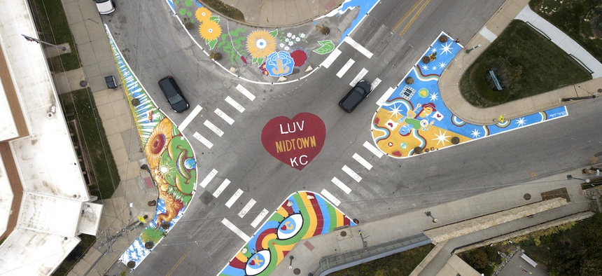 The four-way intersection is buffeted by four curb expansions featuring murals, which shorten crosswalks and reshape the streets.