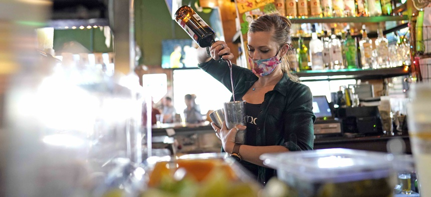 Bartender Alyssa Dooley makes a cocktail at Mo's Irish Pub, Tuesday, March 2, 2021, in Houston. Texas Gov. Greg Abbott announced Tuesday that he is lifting business capacity limits and the state's mask mandate starting next week.